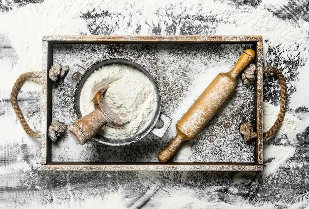 Farine dans un bol avec rouleau à pâtisserie dans une boîte en bois sur la table en pierre