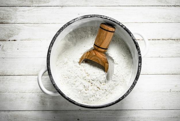 Farine dans une casserole. sur une table en bois blanche.