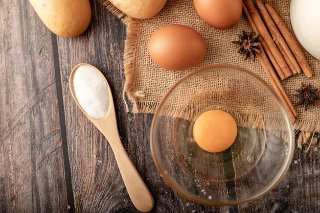 Farine dans une cuillère en bois et des œufs dans un verre sur le sac