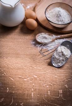Farine dans cuillère cuillère et bol oeufs pichet lait sur planche de bois