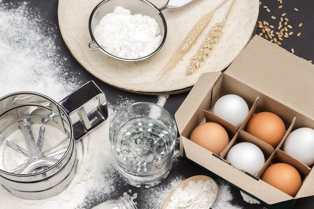 La farine dans des cuillères en bois, un tamis et un bocal en verre avec des œufs en boîte et un verre d'eau