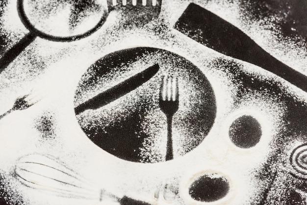 Farine sur fond noir avec des formes d'éléments de cuisine
