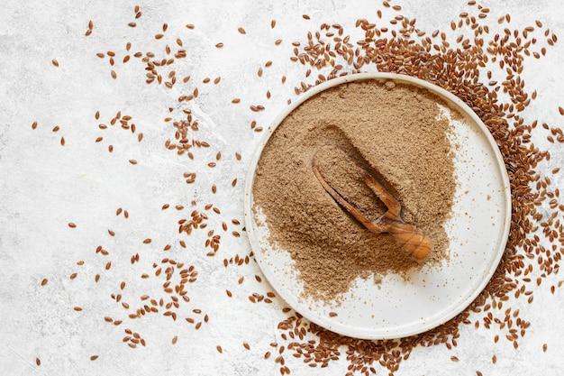 Farine de graines de lin crues dans une assiette en céramique avec une cuillère vue de dessus
