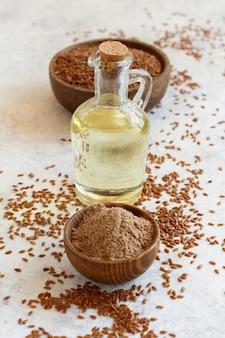 Farine de graines de lin crues, huile et graines avec une cuillère en gros plan sur un tableau blanc