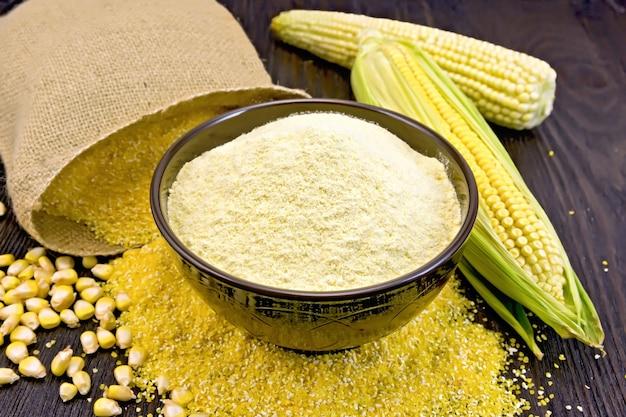Farine de maïs dans un bol sur le gruau, les épis et les grains, un sac sur un fond de planches de bois