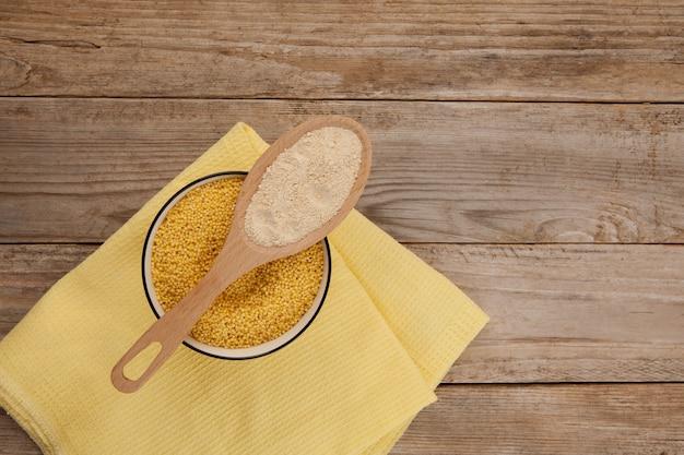 Farine de millet décortiqué et grain dans un bol sur une vieille table en bois, vue de dessus