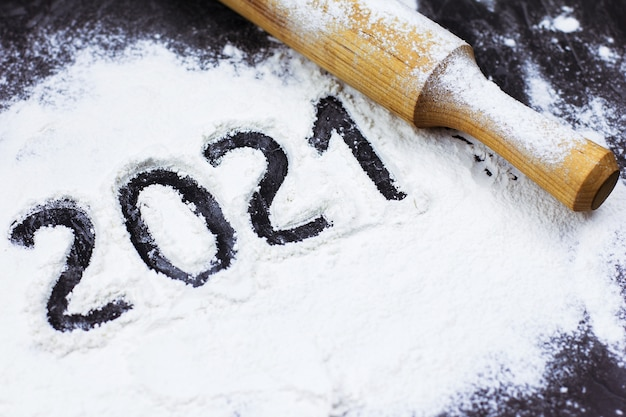 Farine sur un mur noir sous forme de nombres 2021 nouvel an et noël cuisiner à la maison