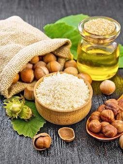 Farine de noisette dans un bol, noix dans un sac, une cuillère, de l'huile dans un bocal en verre et une branche d'aveline avec des feuilles sur fond de planche de bois