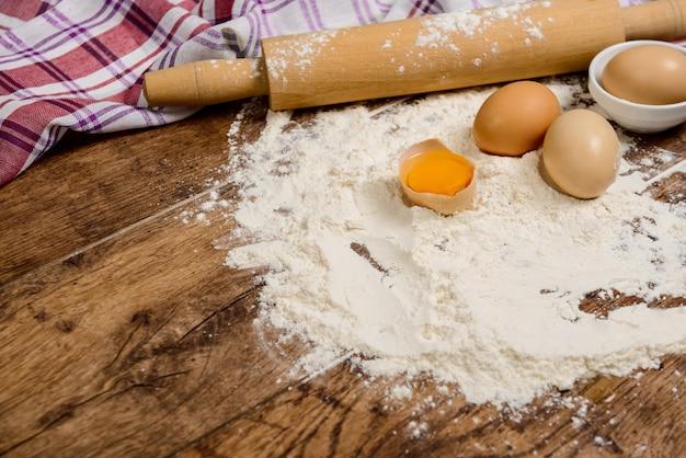 Farine, œufs, sel, serviette, rouleau à pâtisserie sur table en bois prêt pour la cuisson