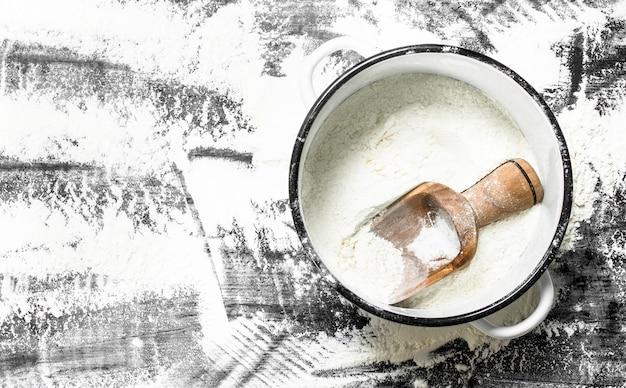 Farine à la pelle dans une casserole. sur la table en pierre.