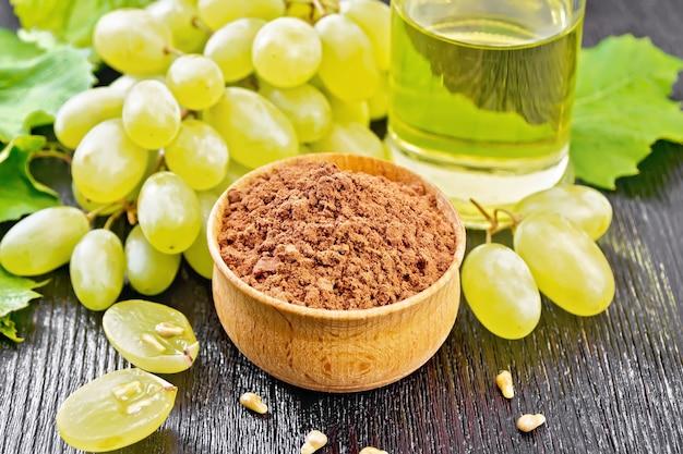 La farine de pépins de raisin dans un bol, l'huile dans un pot et les baies de raisin sur fond de planche de bois