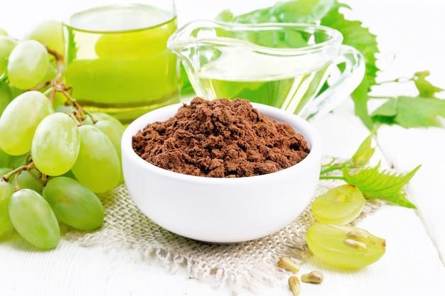 Farine de pépins de raisin dans un bol sur le sac, huile dans un bocal et saucière