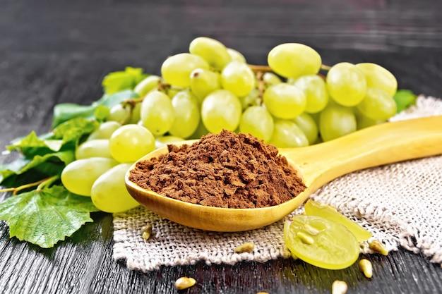 Farine de pépins de raisin dans une cuillère sur une serviette en toile de jute, raisins verts sur fond de planche de bois foncé