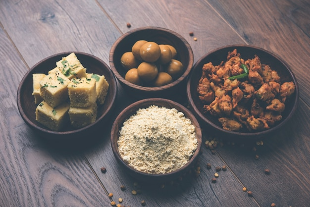 Farine de pois chiches ou poudre de besan dans un bol en céramique ou en bois avec une collation gujrati dhokla, un bajji ou un bhaji à l'oignon et un laddu ou un laddoo sucré