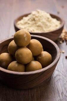 Farine de pois chiches ou poudre de besan dans un bol en céramique ou en bois avec du laddu ou du laddoo sucré