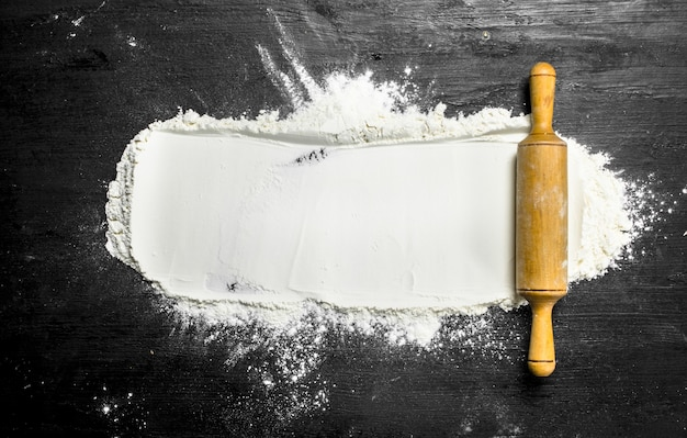Farine avec rouleau à pâtisserie sur le tableau noir