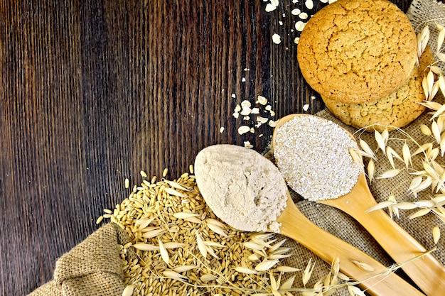 La farine et le son d'avoine en cuillère, les tiges d'avoine et les biscuits à l'avoine sur le sac sur un fond de planches en bois