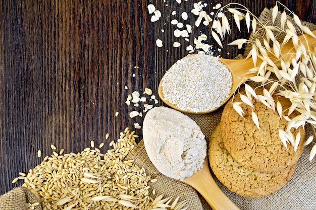 La farine et le son d'avoine dans une cuillères, des tiges d'avoine, du gruau et des biscuits sur un fond de sac sur planche de bois