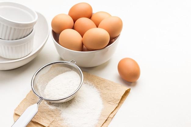 Farine et tamis sur papier. faire dorer les œufs de poule dans un bol. vaisselle en céramique blanche. vue de dessus. copier l'espace
