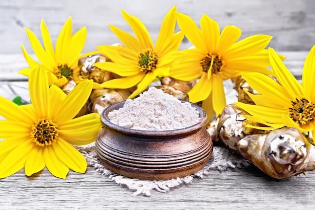 Farine de topinambour dans un bol en argile sur une toile de jute avec des fleurs et des légumes sur fond d'une vieille planche de bois