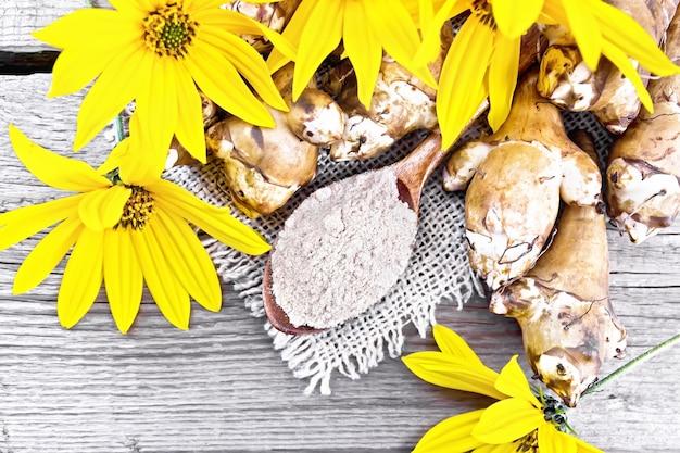 Farine de topinambour dans une cuillère sur une toile de jute avec des fleurs et des légumes sur fond d'une vieille planche de bois d'en haut