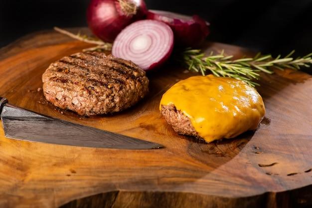 Farm organic burger, oignon violet et fromage fondant sur une table en bois rustique