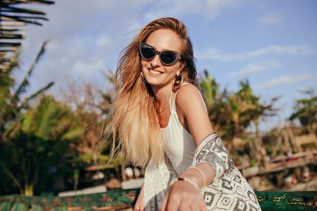 Fascinante femme bronzée riant sur la nature. femme en lunettes de soleil noires à la mode exprimant le bonheur en bonne journée à la station.