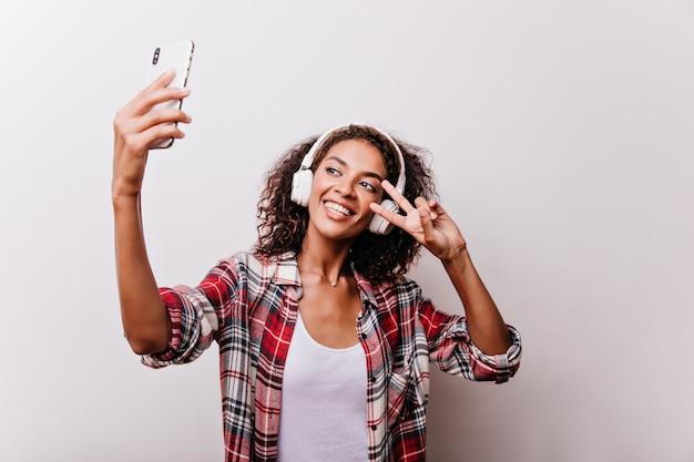 Fascinante fille aux cheveux noirs posant avec signe de paix pour selfie. jolie jeune femme dans un casque blanc tenant le smartphone.