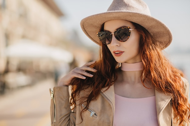 Fascinante jeune femme avec une longue coiffure en regardant autour de lunettes