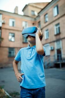 Fasciné petit garçon utilisant des lunettes de réalité virtuelle vr. de plein air