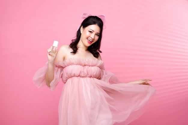 Fashion beauty woman a les cheveux noirs expriment un sentiment d'amour heureux. fille asiatique porte une robe rose sur un mur de ton rose tenir la lotion de soin de la peau de beauté et appliquer sur la main du visage, espace de copie