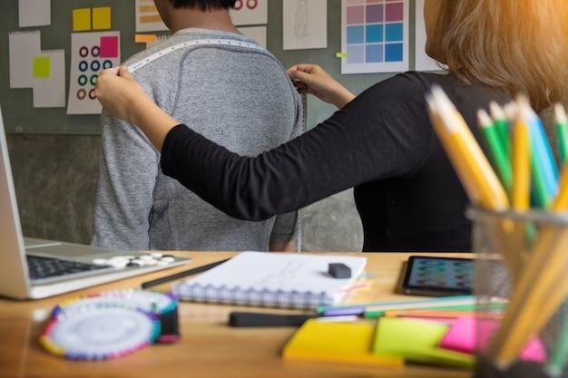 Fashion designer mesure sur chest behind of men pour un tailleur sur mesure pour un jeune homme d'affaires.