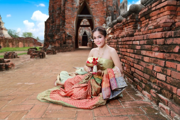 Fashion fille asiatique en costume traditionnel thaïlandais dans un temple antique avec fleur au volant à la main