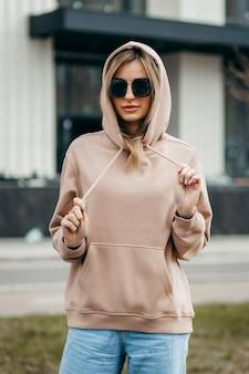 Fasion femme blonde en lunettes à capuche surdimensionnées marron et maquette de jean bleu pour la conception de logo ou de marque