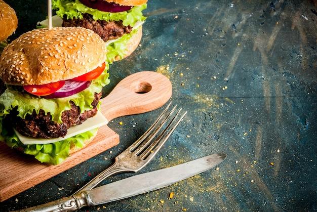 Fast food. aliments malsains. délicieux hamburgers frais et savoureux avec escalope de boeuf, légumes frais et fromage sur béton bleu foncé. fond