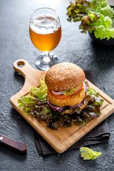 Fast food. un gros hamburger et un verre de bière. sur un fond sombre.