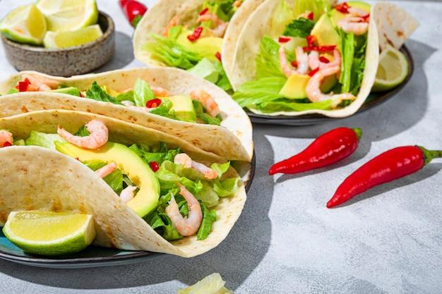 Fast food mexicain traditionnel tacos mexicains aux crevettes et à l'avocat avec des poivrons au citron vert et aux épices en gros plan