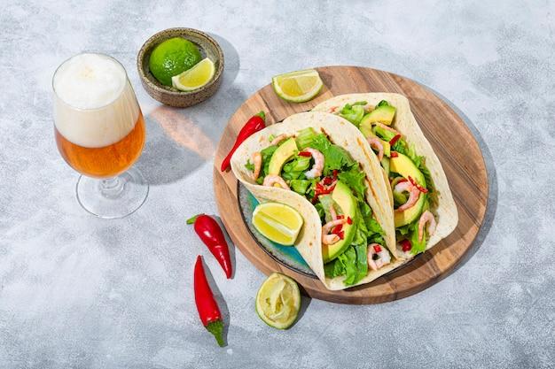 Fast food mexicain traditionnel tacos mexicains aux crevettes et à l'avocat avec des poivrons au citron vert et aux épices et léger