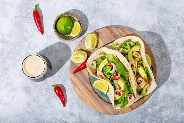 Fast food mexicain traditionnel tacos mexicains aux crevettes et à l'avocat avec des poivrons au citron vert et aux épices et noir