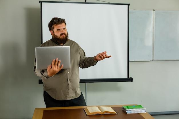 Fat prof à lunettes avec ordinateur portable sur blanc