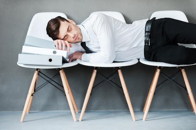 Fatigué après avoir travaillé dur. jeune homme fatigué gardant les yeux fermés