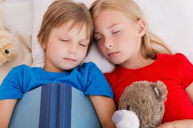 Fatigué après une journée active. vue de dessus de deux enfants mignons dormant en position couchée ensemble