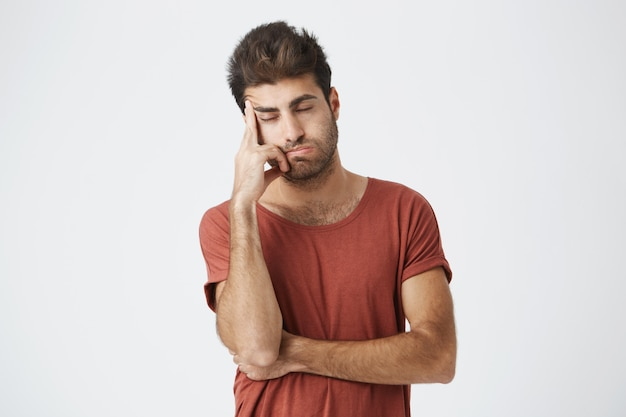 Fatigué barbu espagnol portant un t-shirt rouge tenant la main sur le front à la recherche de stressant ayant des maux de tête après une situation de conflit au travail. les gens, le stress et la migraine.