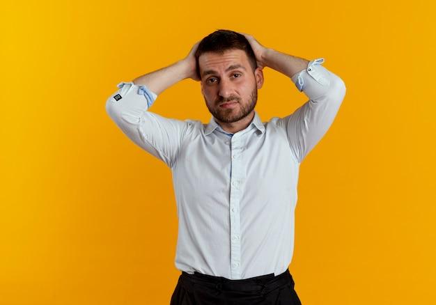 Fatigué bel homme tient la tête à deux mains isolé sur un mur orange