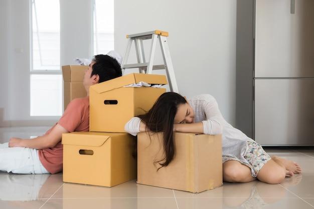 Fatigué couple asiatique dort au déménagement des boîtes