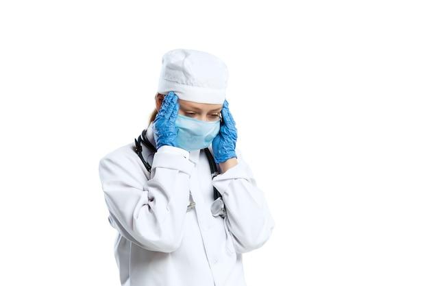 Fatigué, désespoir. jeune femme médecin avec stéthoscope et masque facial sur studio blanc.