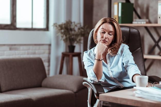 Fatigué et épuisé. belle femme d'affaires mature se sentant fatiguée et épuisée à la fin de la journée