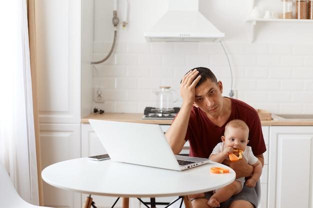 Fatigué épuisé homme beau pigiste vêtu d'une chemise bordeaux, posant dans une cuisine blanche, assis devant un ordinateur portable avec un bébé dans les mains, ayant des maux de tête.