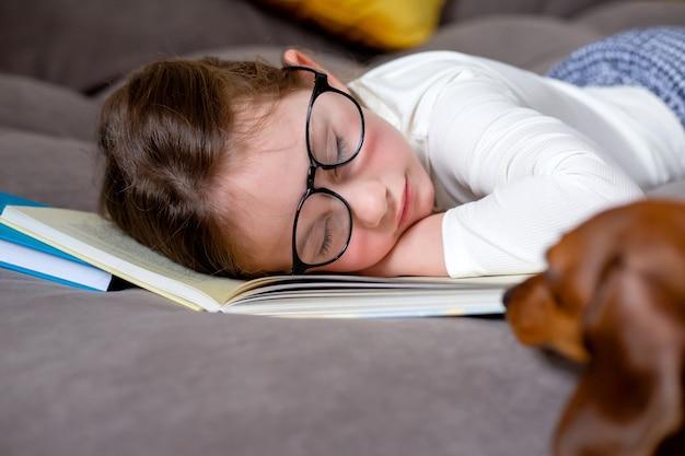 Fatigué d'étudier et de lire la petite fille mignonne avec des lunettes dort sur le lit sur un livre ouvert