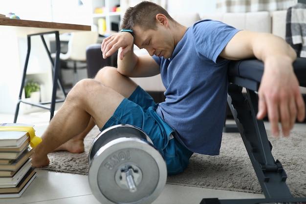 Fatigué d'exercices sportifs, un gars est assis à la maison